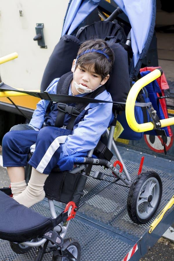 Неработающий мальчик на подъеме кресло-коляскы шины стоковая фотография