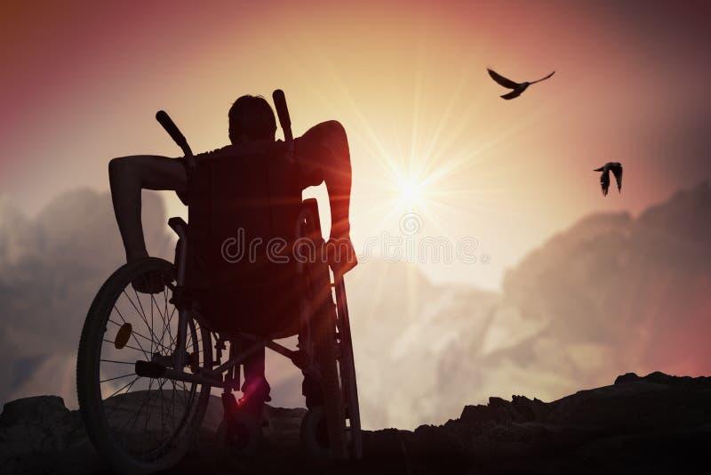 Неработающий с ограниченными возможностями человек имеет надежду Он сидит на кресло-коляске и протягивает руки на заходе солнца стоковое фото rf
