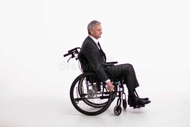 Неработающий человек в кресло-коляске в костюме стоковое фото rf