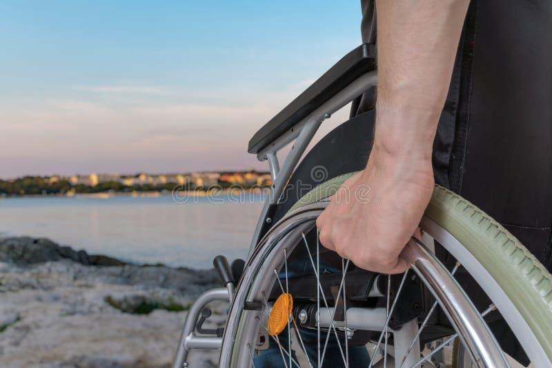 Неработающий человек сидя на кресло-коляске около моря на заходе солнца стоковая фотография rf