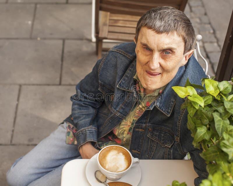 Неработающий человек при церебральный паралич сидя кафе стоковое фото rf