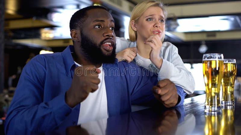 Нервные biracial пары поддерживая любимую команду спорта, наблюдая спичку онлайн стоковая фотография