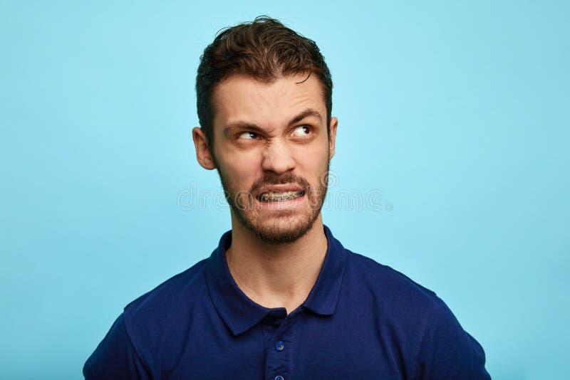 Нервный человек в щелкать футболки, смотря космос экземпляра стоковое фото rf