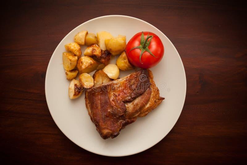 Нервюры свинины с картошкой с томатом стоковое фото