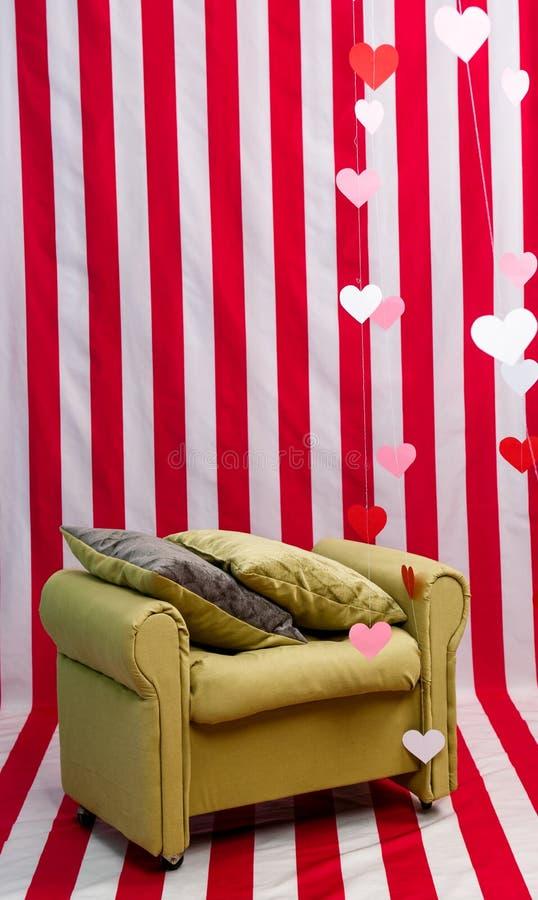 Нереальное изображение мягкого бежевого кресла сравнивая с обнажанной белыми и красными стеной и полом стоковое фото rf