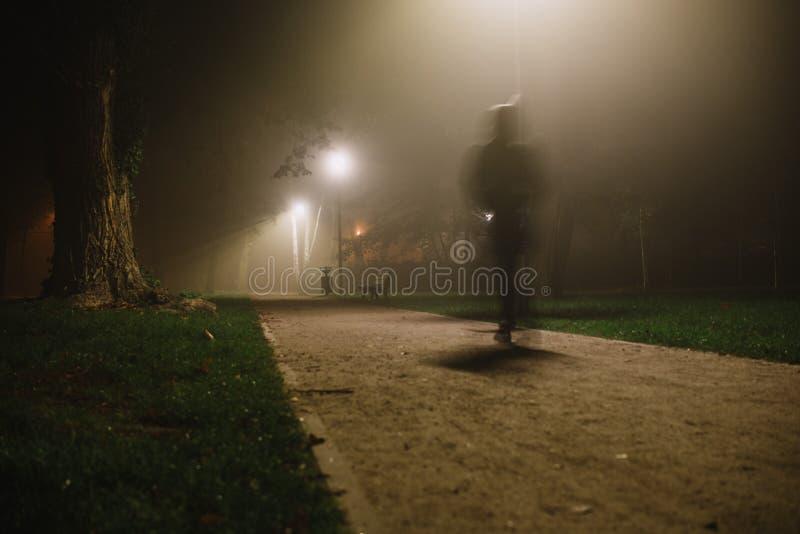 Нерезкость движения людей в парке, ноче и густом тумане стоковые фото