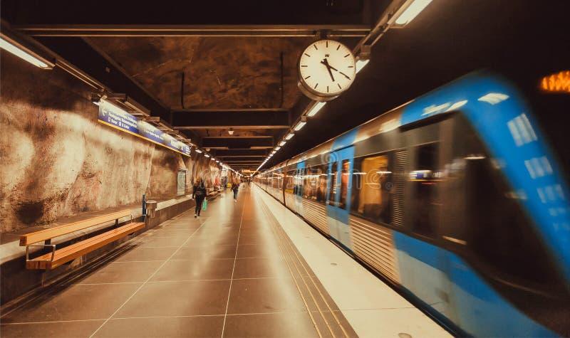 Нерезкость движения от поезда метро управляя прошлой станцией метро с часами стоковое фото