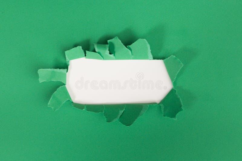 Неровное сорванное отверстие в сорванной бумаге на зеленом цвете стоковая фотография rf