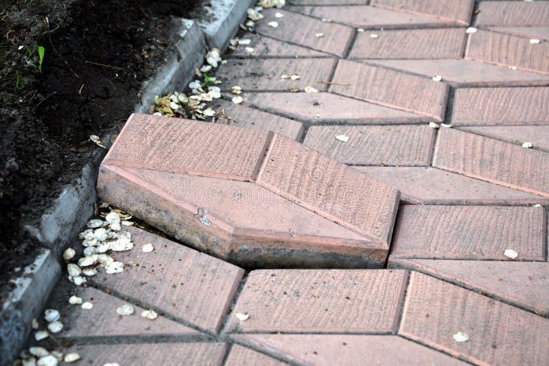 Неровно положенные вымощая плиты Одна плитка над остатками на тротуаре стоковое фото rf