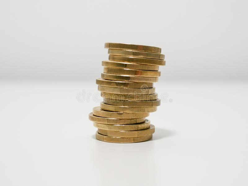Неровный стог монеток одного евро на белом столе около, который нужно свергать сверх стоковые изображения rf