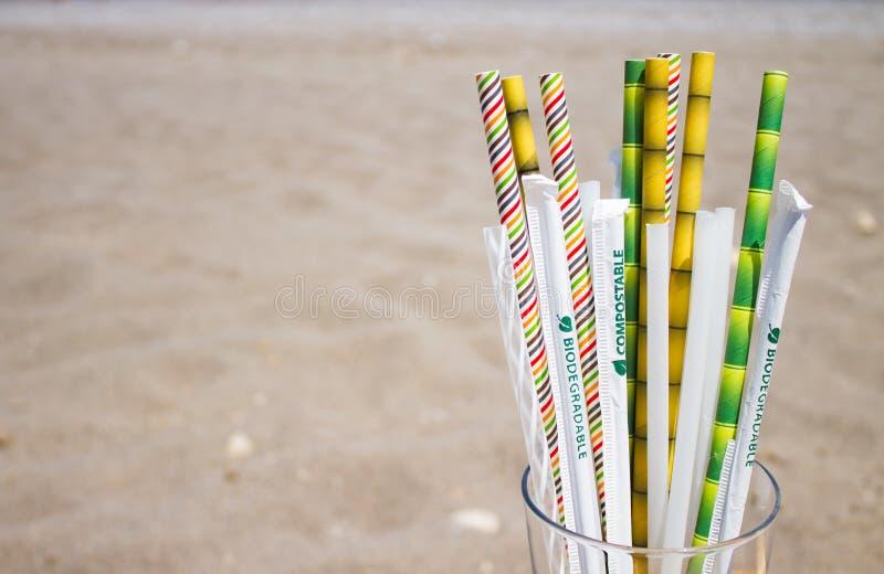 Несколько замен пластиковых трубок, bioplastics и бамбука коктейля в стекле в blured предпосылке с песком на пляже стоковые изображения rf