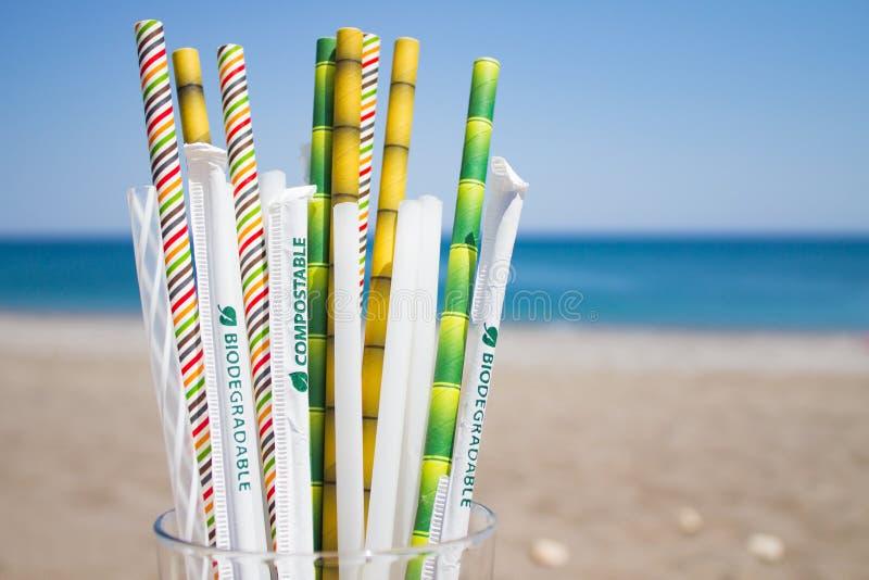 Несколько замен пластиковых трубок, bioplastics и бамбука коктейля в стекле в blured предпосылке с пляжем стоковые изображения