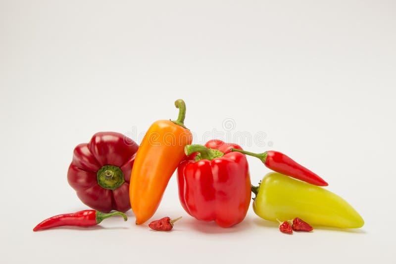 Несколько зрелых сладостных и горячих перцев красного цвета и апельсина на белизне стоковое изображение rf