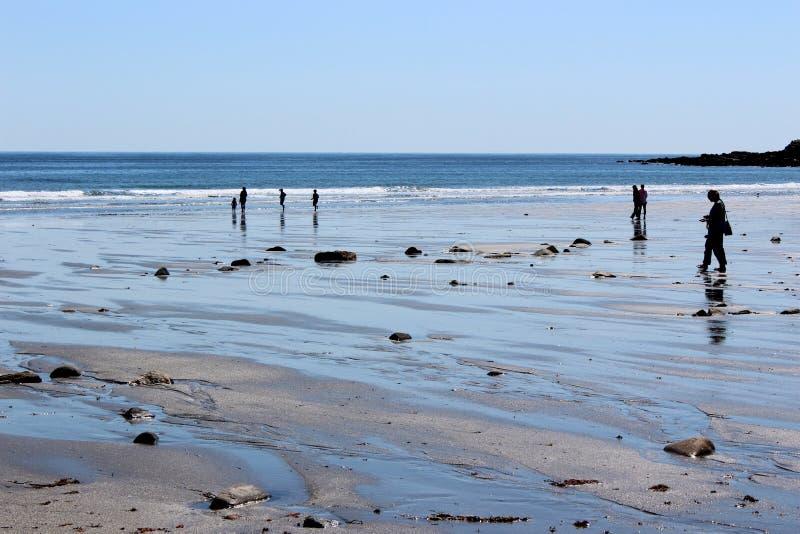 Несколько людей в тени идя вдоль коротких песков приставают к берегу, Мейн, 2018 стоковые фотографии rf