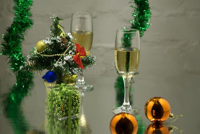 Несколько стекла с шампанским на деревянном столе с шариками рождества, красной ленте с sprig спруса на темном backgro стоковые изображения