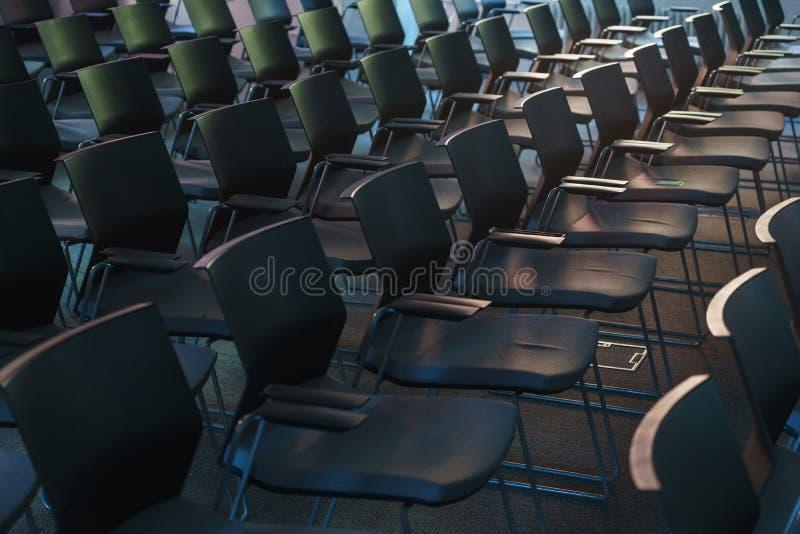 Несколько строк пустых пластичных стульев в аудитории подготовили для речи ` s диктора перед студентами или журналистами стоковое изображение rf