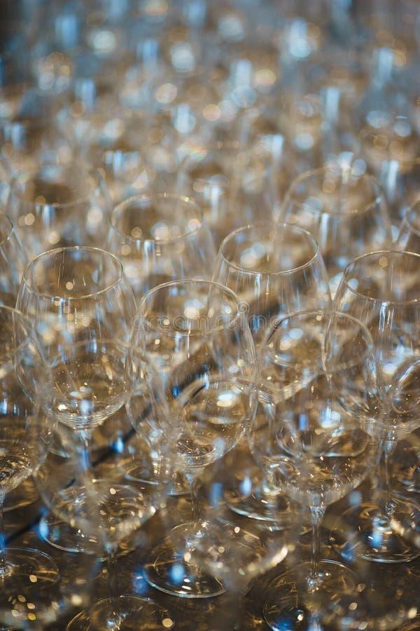 Несколько строк ясно, чистых стекла для вина и шампанское на счетчике подготовленном для напитков стоковое фото