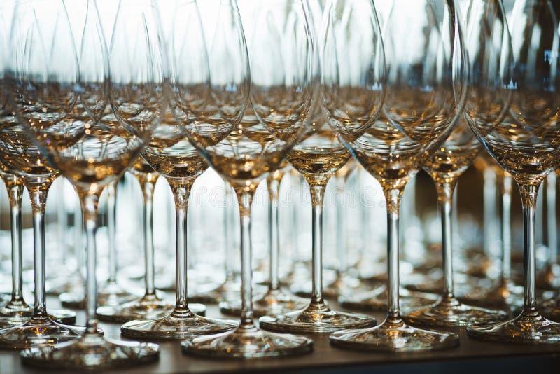 Несколько строк ясно, чистых стекла для вина и шампанское на счетчике подготовленном для напитков стоковая фотография rf