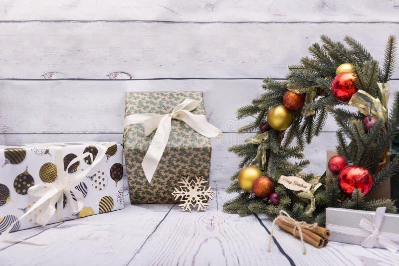 Несколько упакованных подарочных коробок, венок рождества с красным и золотым стоковые фотографии rf