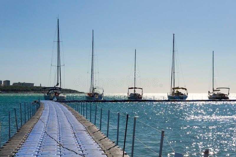 Несколько яхт в ряд припаркованы на пристани Голубое небо и море на заднем плане стоковая фотография