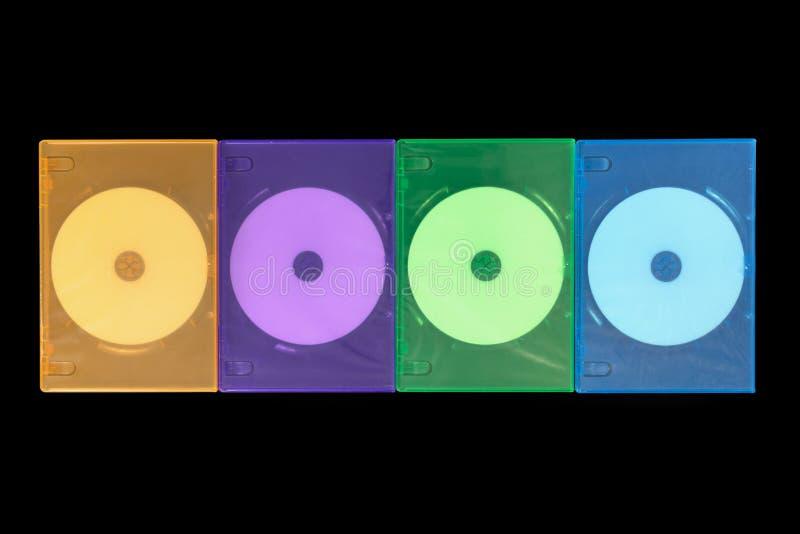 Несколько покрашенных коробок DVD/КОМПАКТНЫЙ ДИСК на черной предпосылке стоковое фото rf