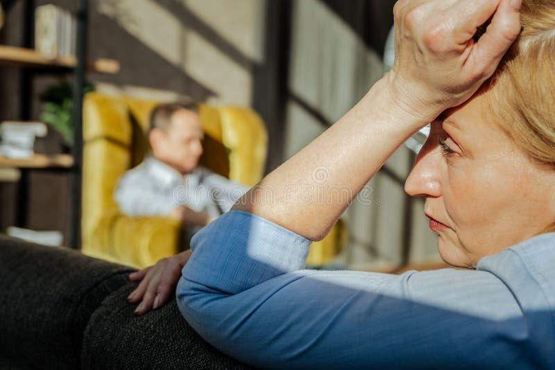 Несчастная белокурая женщина драматически полагаясь на задней части кресла стоковые изображения