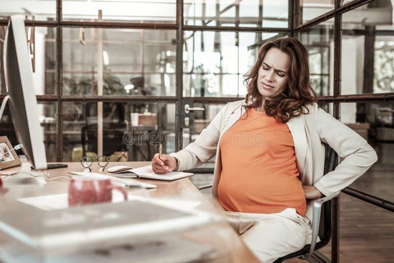 Несчастная длинн-с волосами женщина быть дискомфортный на стуле офиса стоковое фото rf