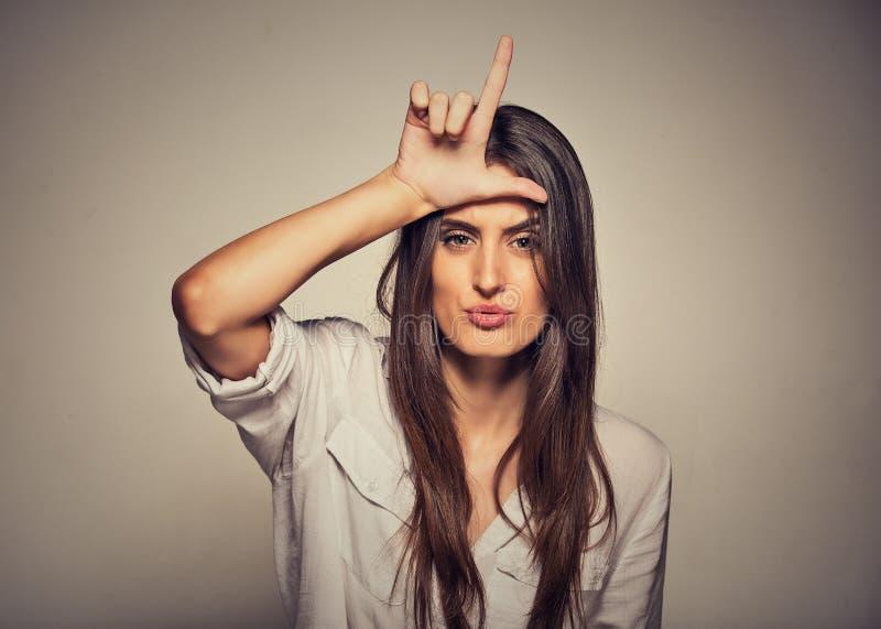 Несчастная женщина давая знак проигравшего на лбе, смотря вас, отвращение на стороне стоковые фотографии rf