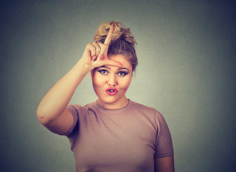 Несчастная женщина давая знак проигравшего на лбе, смотря вас, отвращение на стороне стоковое изображение rf
