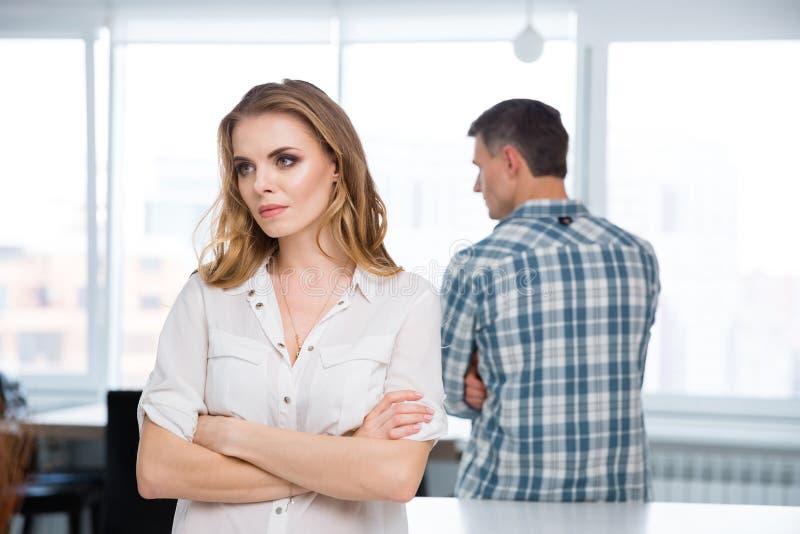 Несчастная женщина в ссоре с ее супругом дома стоковые изображения