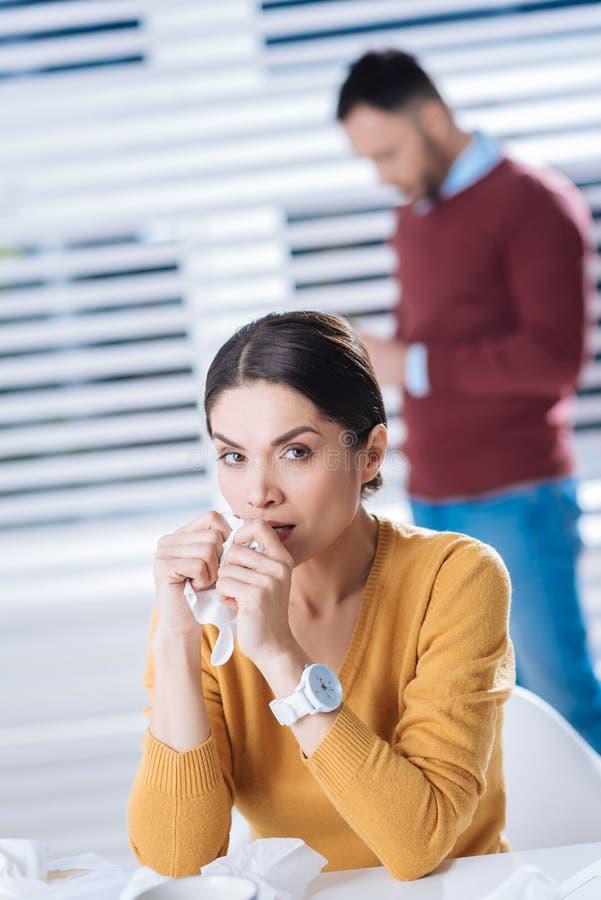 Несчастная женщина держа салфетку пока имеющ идущий нос стоковая фотография rf