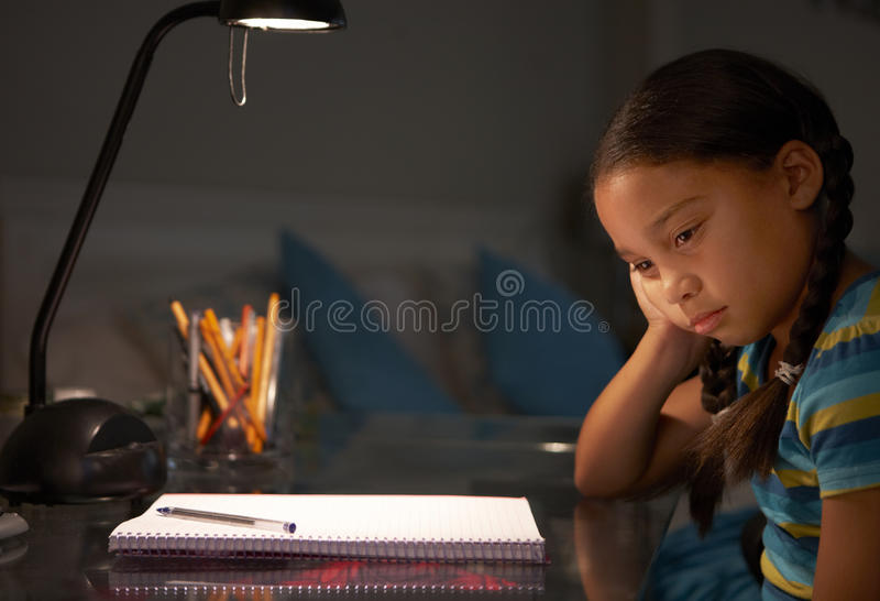 Несчастная маленькая девочка изучая на столе в спальне в вечере стоковое изображение rf