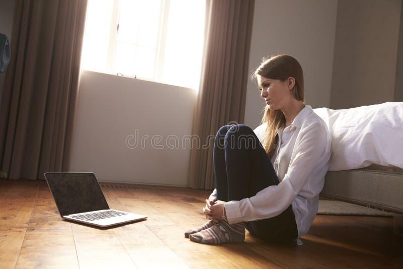Несчастная молодая женщина быть задранное онлайн с компьтер-книжкой стоковая фотография