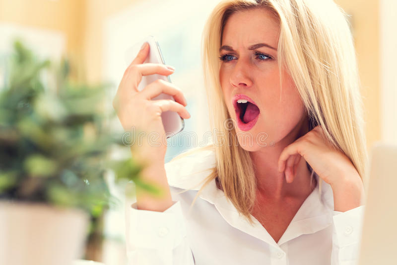 Несчастная молодая женщина говоря на телефоне стоковые фотографии rf