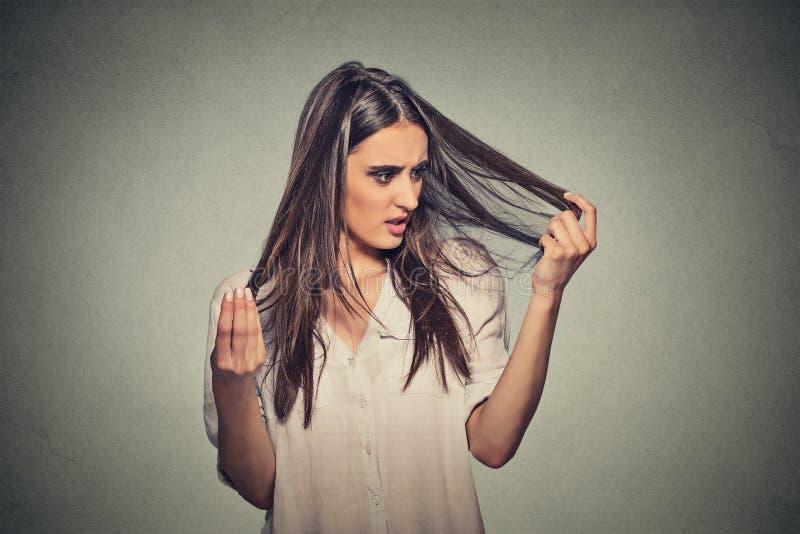 Несчастная разочарованная молодая женщина удивила ее проигрышные волосы стоковые изображения