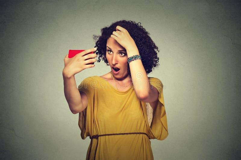 Несчастная разочарованная молодая женщина удивила ее проигрышные волосы, волосяный покров отступать стоковая фотография