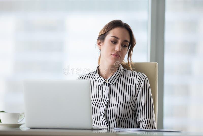 Несчастная уставшая молодая женщина сидя на рабочем месте стоковое фото rf