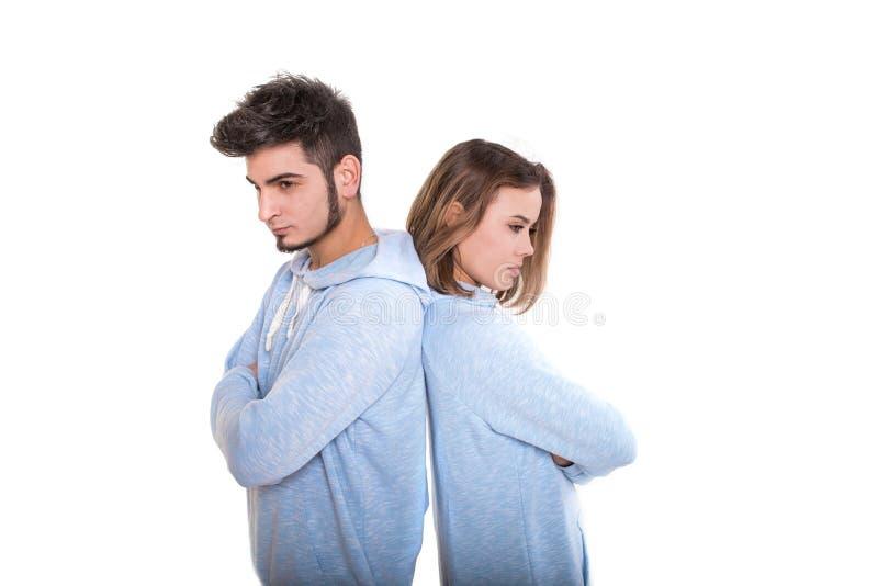Несчастные молодой человек и женщина стоят назад один другого и не говорят стоковое фото rf