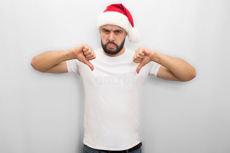 Несчастный молодой человек в красных стойках и представлениях шляпы на камеру Он смотрит его Гай держит его большие большие пальц стоковые фотографии rf