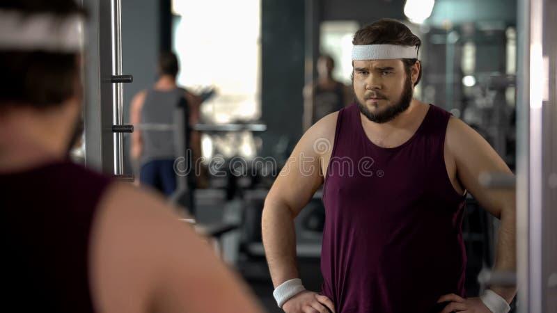 Несчастный полный человек смотря его отражение зеркала в спортзале, диете и спорте стоковая фотография rf