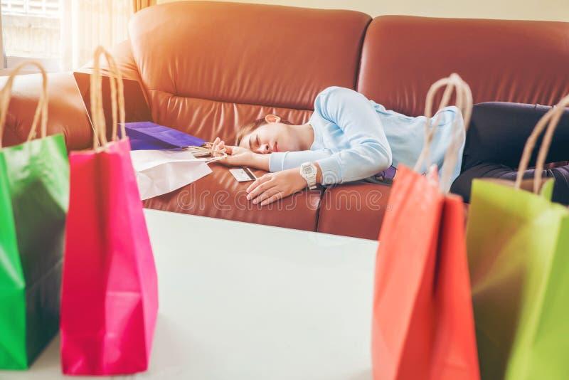 Несчастный сон молодой женщины на хозяйственных сумках софы и владения с de стоковое фото