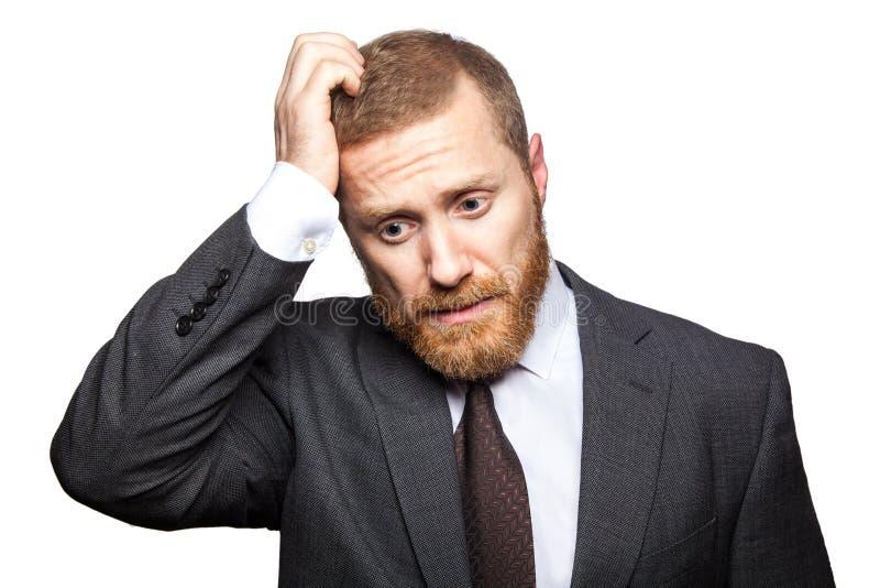 Несчастный унылый бизнесмен думая с его рукой на голове Изолированный на белизне, стоковое изображение rf