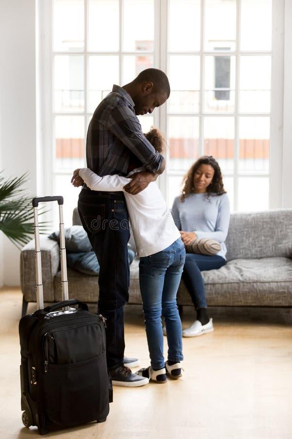 Несчастный черный отец выходя дочь семьи плача дома стоковое фото