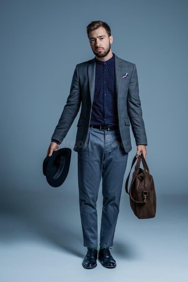 Неудовлетворенный молодой человек в костюме стоя с шляпой и кожаной сумкой стоковая фотография rf