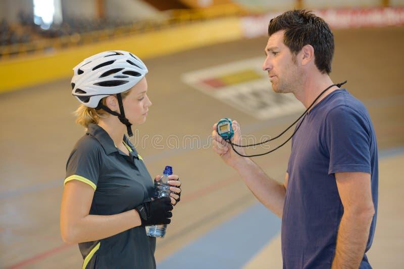 Неудовлетворённый тренер показывая секундомер к велосипедисту стоковая фотография