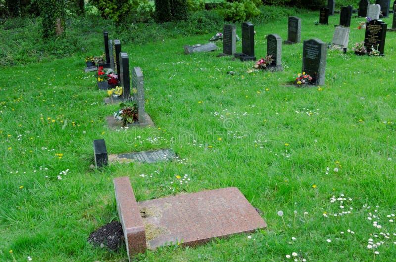 Неустойчивые и опасные надгробные камни клали плоско стоковые изображения rf