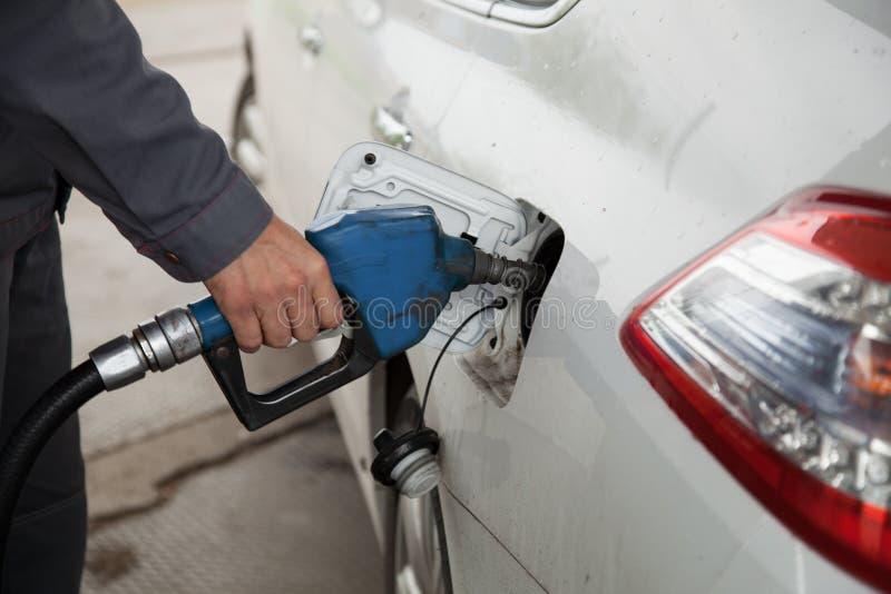 Нефть мужской руки нагнетая в автомобиль на бензоколонке стоковая фотография