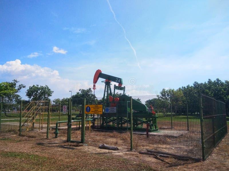 Нефть нефтедобывающих промышленностей Бруней на насосе земли берега стоковое фото rf