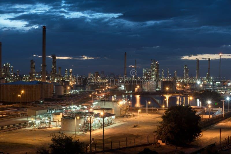 Нефтяная промышленность нефти и газ - рафинадный завод на сумерках - фабрика - нефтехимический завод стоковые фото