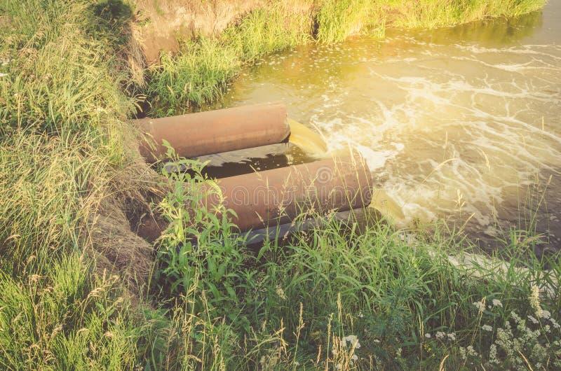 Нечистоты от сточной трубы загрязняют озеро/подачу сточных водов от трубы водопровода в озеро в восходе солнца стоковые изображения